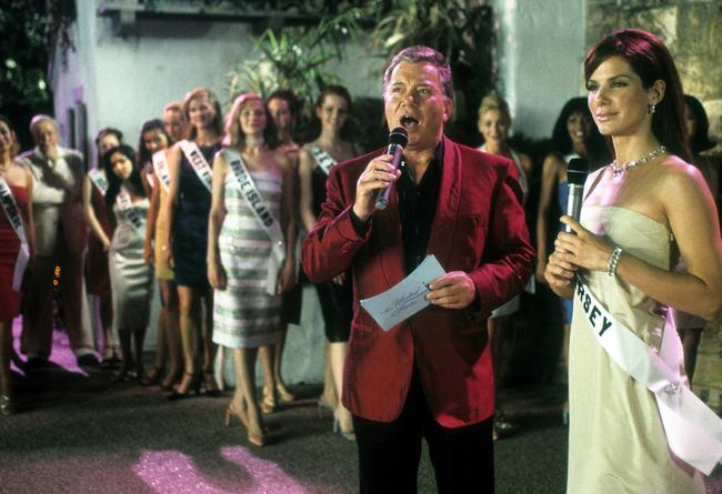 William Shatner speaks into a microphone next to Sandra Bullock in a scene from the film 'Miss Congeniality', 2000